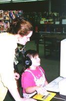 An adult helps a child using a computer