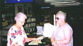A patron receives assistance at the library desk